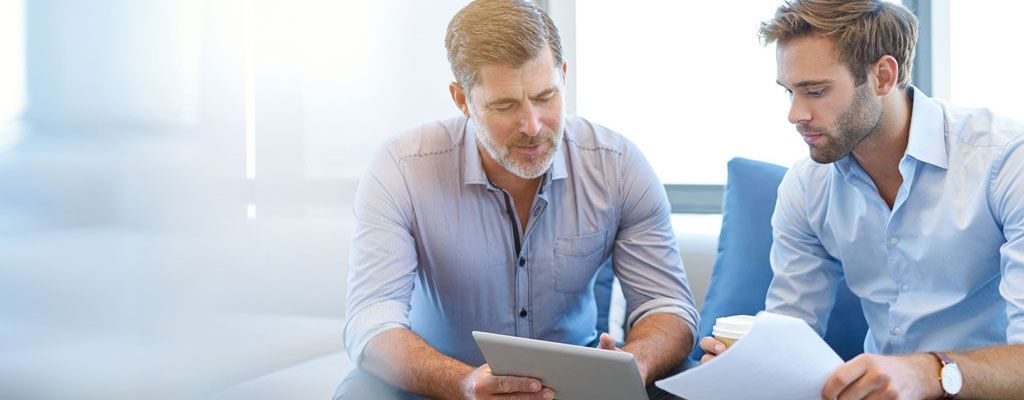 Two men are sat looking at a tablet and discussing